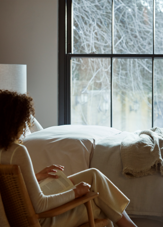 woman sitting beside vispring bed reading a book winter outside the window
